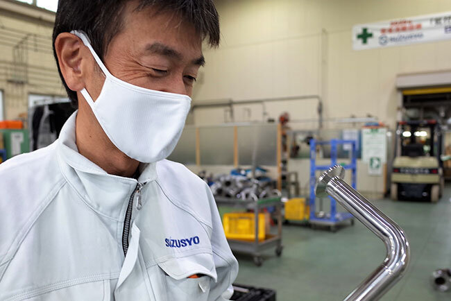 サニタリー配管を見つめる鈴木社長。ICTの活用で経営環境は大きく進化した